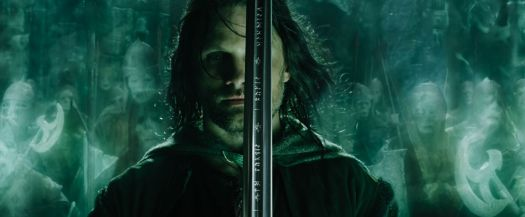 Aragorn stands with his sword in front of his face, ready to lead the green-glowing army of the dead in Lord of the Rings