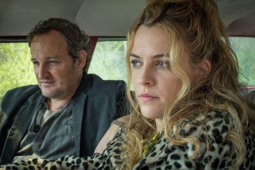 Jason Clarke as Carl Henderson , Riley Keough as Sandy Henderson driving a car in The Devil All the Time