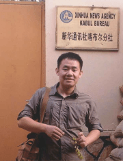 """Xiyue Wang stands with a bag on his shoulder and in front of a sign reading """"Xinhua News Agency Kabul Bureau"""""""