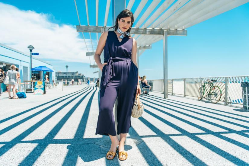 A model standing under a bridge wearing a jumpsuit