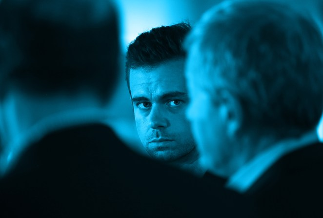Twitter CEO Jack Dorsey (C) looks on as Senate Finance Committee Chairman Max Baucus (R) (D-MT) and House Ways and Means Committee Chairman Dave Camp (L) (R-MI) speak to reporters while touring the Square headquarters