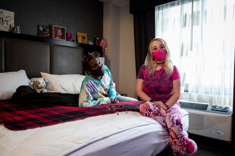 Nunu Jefferson and Ashley Belcher watch television in hotel room on the Lower East Side, Thursday, Apr. 29, 2021.