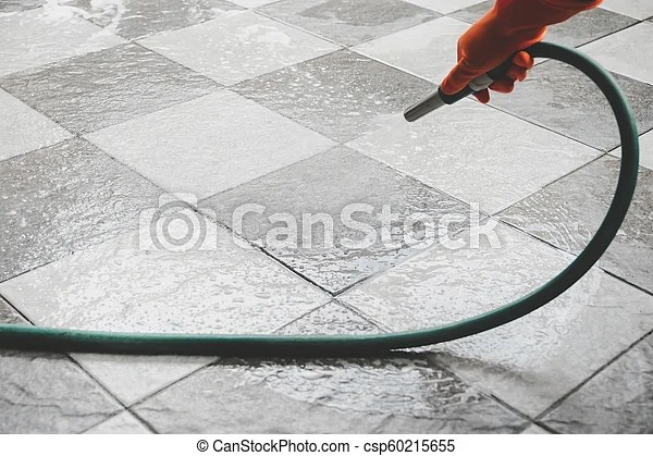clean the floor with a water hose hand of man wearing orange rubber gloves is use a hose to clean the tile floor canstock