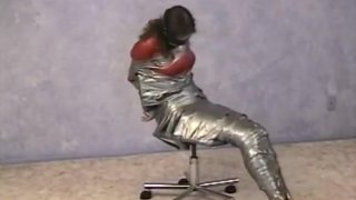 Secretary bound in tape, gagged and blindfold by intruder thumb