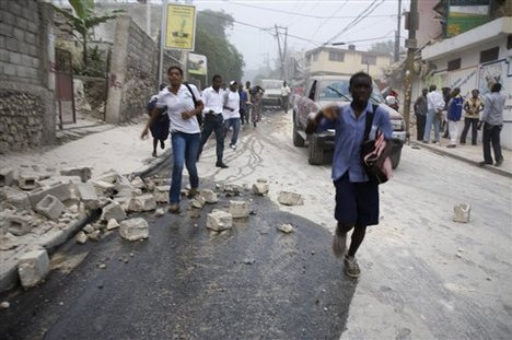 People run in the streets after an earthquake struck Port-au-Prince, Tuesday
