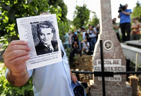 A man holds a leaflet with a picture of late communist dictator Nicolae Ceausescu as media and members of the public gather around his freshly dug up grave in the background at the Ghencea cemetery in Bucharest, Romania, Wednesday, July 21, 2010.