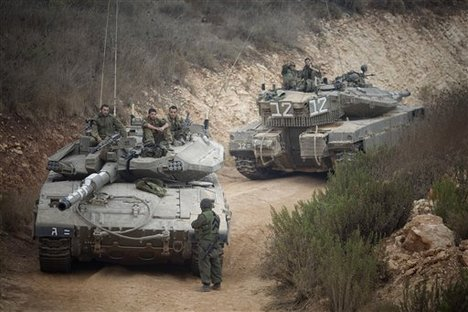 Israeli soldiers sit on top of their tank near the site of an exchange of fire between Israeli and Lebanese troops along the border between Israel and Lebanon, Wednesday, Aug. 4, 2010.