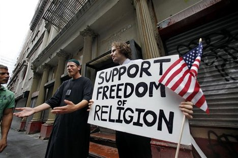 Abdul Malik, center, an American Muslim from Philadelphia, and Matt Sky, right, a Web developer from Manhattan, N.Y., stand in front of a proposed site for an Islamic cultural center as they explain their support for its construction to passers-by in New York, Monday, Aug. 23, 2010.