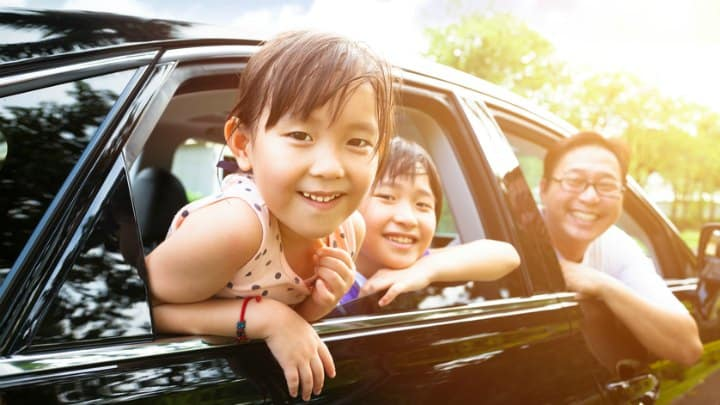 happy little girl with family sitting in the car