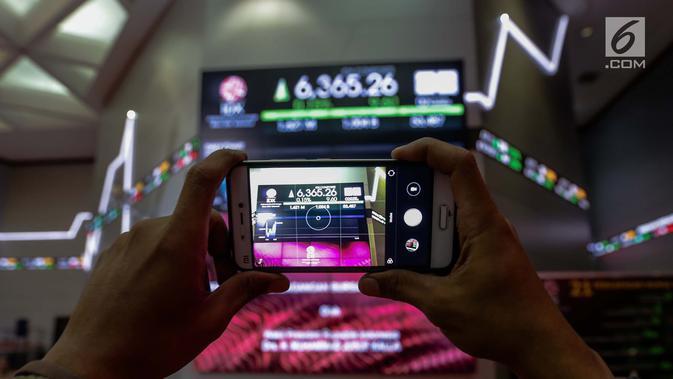 Pengunjung mengambil foto layar indeks harga saham gabungan yang menunjukkan data di Bursa Efek Indonesia, Jakarta, Selasa (2/1). Sebelumnya, Perdagangan Indeks Harga Saham Gabungan (IHSG) 2017 ditutup pada level 6.355,65 poin.(Liputan6.com/Faizal Fanani)