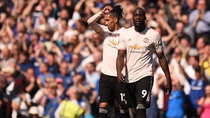Pemain Manchester United, Romelu Lukaku dan Chris Smalling tampak kecewa usai ditaklukkan Everton pada laga Premier League di Goodison Park, Minggu (21/4). Everton menang 4-0 atas Manchester United. (AFP/Oli Scarff)