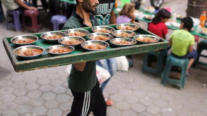 Seorang relawan membawa makanan ke meja sebagai orang menunggu untuk makan makanan Iftar mereka untuk berbuka puasa di meja amal yang menawarkan makanan gratis selama bulan suci Ramadan di Kairo, Mesir