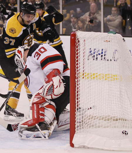 BOSTON - NOVEMBER 15:  Patrice Bergeron #37 of the Boston Bruins gets the assist as the puck slips past Martin Brodeur #30 of the New Jersey Devils on November 15 2010 at the TD Garden in Boston Massachusetts.  (Photo by Elsa/Getty Images)