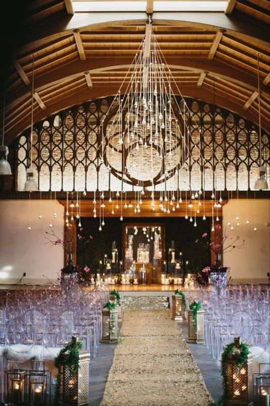 industrial wedding venue with Edison bulb lamps and gold sequin aisle runner