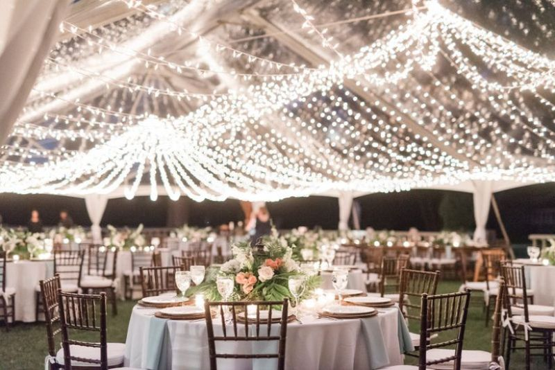clear wedding reception tent with string lights and round banquet tables