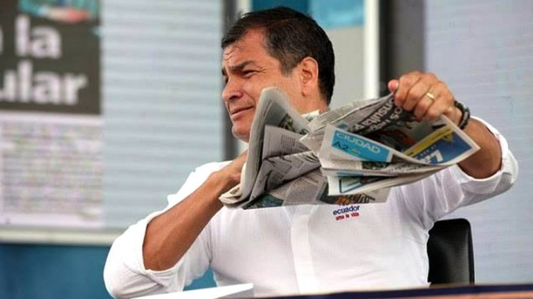 El presidente ecuatoriano, Rafael Correa, rompe un periódico