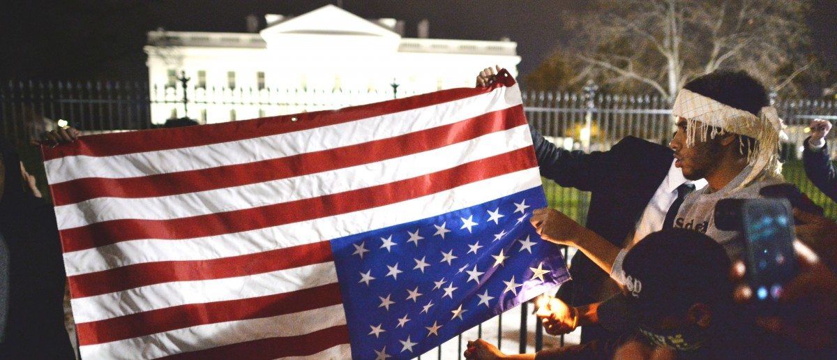 Protesters try unsuccessfully to burn an upside down US flag during a protest outside the White House in Washington, DC on November 25, 2014, one day after a grand jury decision not to prosecute a white police officer for the killing of an unarmed black teen in Ferguson, Missouri. (Photo: MLADEN ANTONOV/AFP/Getty Images)