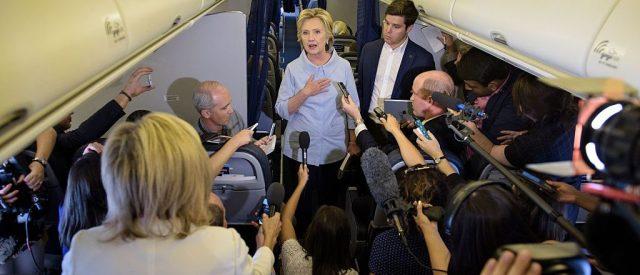 Democratic presidential nominee Hillary Clinton speaks to the press onboard her plane September 5, 2016 above Iowa. / AFP / Brendan Smialowski (Photo credit should read BRENDAN SMIALOWSKI/AFP/Getty Images)