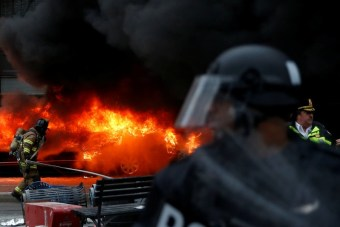 Police and firefighters stand near a limousine which was set ablaze during a protest against U.S. President Donald Trump on the sidelines of the inauguration in Washington, D.C., U.S., on January 20, 2017. REUTERS/Adrees Latif