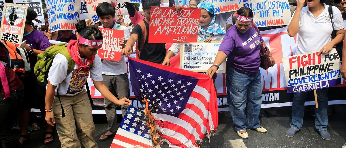 Protesters burn a U.S. flag and a mock flag with pictures of U.S. President-elect Donald Trump outside the U.S. embassy in metro Manila, Philippines January 20, 2017.       REUTERS/Romeo Ranoco