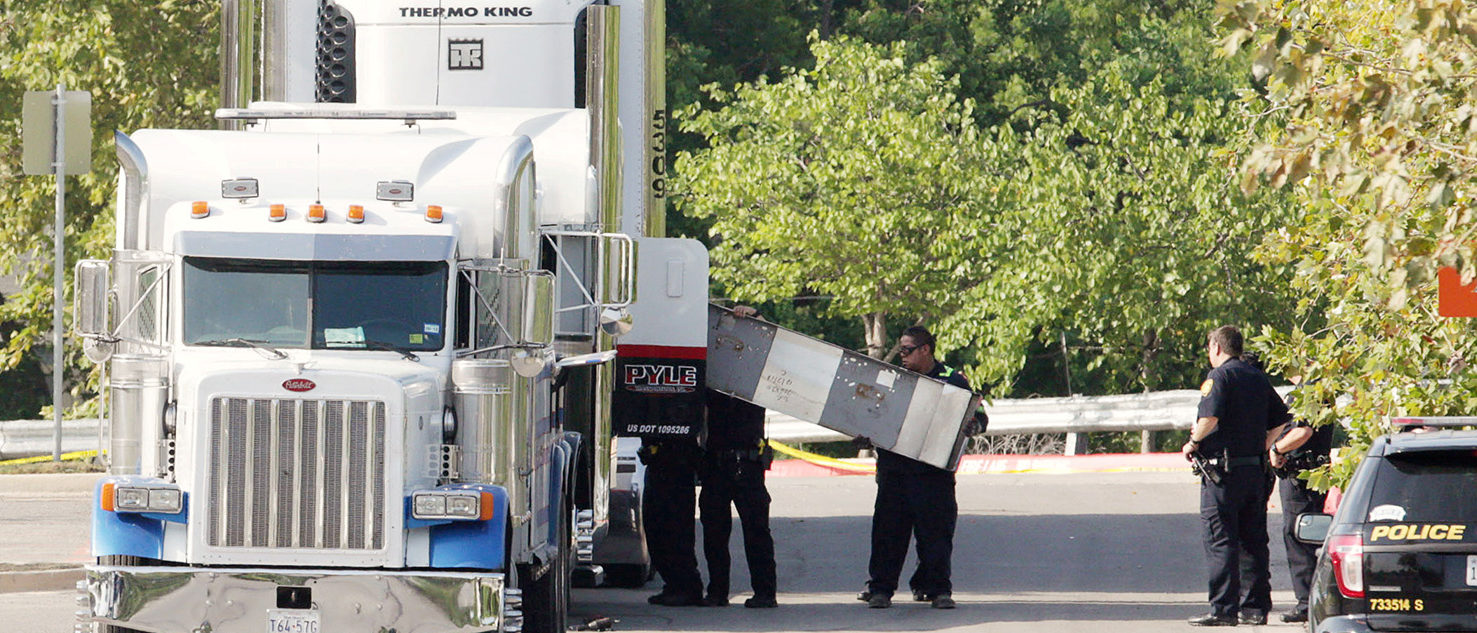 Police officers work on a crime scene after eight people believed to be illegal immigrants being smuggled into the United States were found dead inside a sweltering 18-wheeler trailer parked behind a Walmart store in San Antonio, Texas, U.S. July 23, 2017.  (PHOTO: REUTERS/Ray Whitehouse)