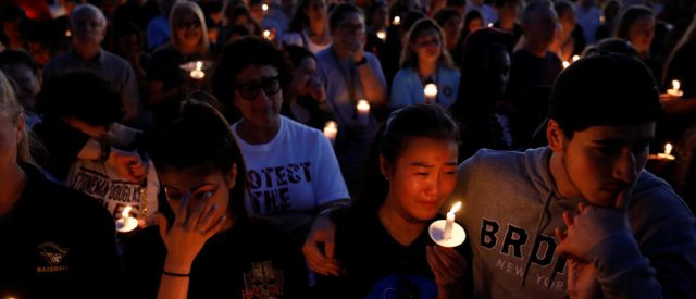 People attend a candlelight vigil for victims of yesterday's shooting at nearby Marjory Stoneman Douglas High School, in Parkland, Florida, U.S. February 15, 2018. REUTERS/Carlos Garcia Rawlins