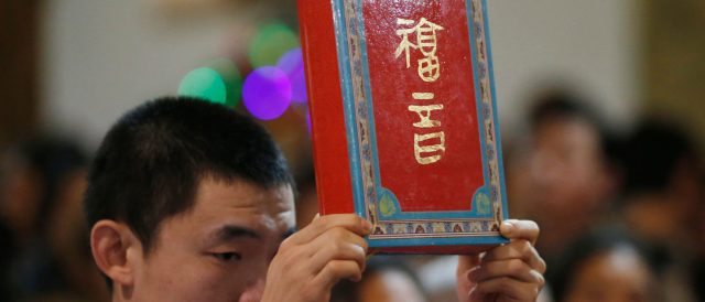 """A page boy holds up a bible during a Christmas mass at a Catholic church in Beijing December 24, 2014. Christmas is not a traditional festival in China but is growing in popularity, especially in more metropolitan areas where young people go out to celebrate, give gifts and decorate their homes. The words on the cover read, """"gospel"""". REUTERS/Kim Kyung-Hoon 