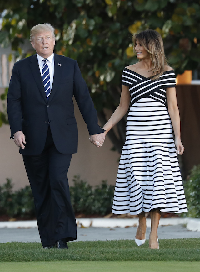 U.S. President Donald Trump and first lady Melania Trump hold hands as walk with Japan's Prime Minister Shinzo Abe and Abe's wife Akie (not pictured) as they arrive for a dinner at Trump's Mar-a-Lago estate in Palm Beach, Florida, U.S., April 17, 2018. REUTERS/Kevin Lamarque - HP1EE4H1T59QL