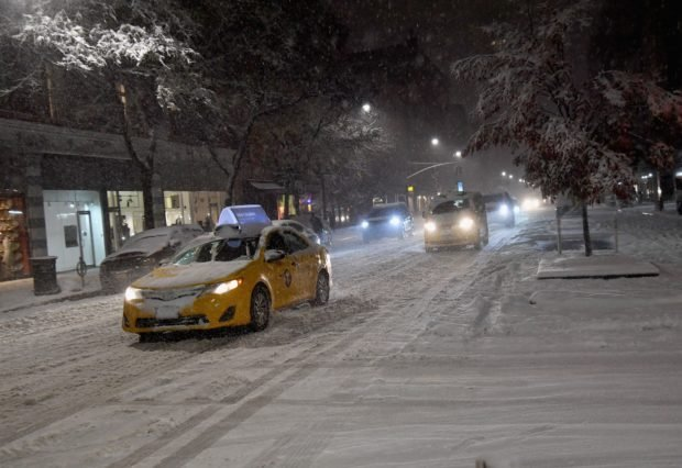 Cars are driving through snow and ice in Manhattan on November 15, 2018 in New York. - The National Weather Service is predicting snowfall totals of 2 to 4 inches in New York City. (Photo by Angela Weiss / AFP) (Photo credit should read ANGELA WEISS/AFP/Getty Images)