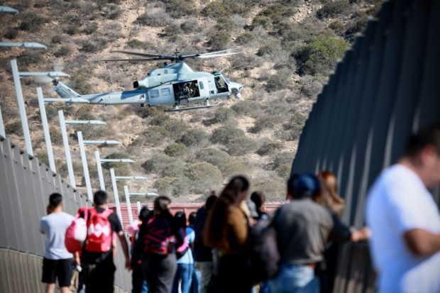 A United States Military helicopter flies past a pedestrian bridge after the closing of the United States-Mexico border was ordered on November 25, 2018 at the San Ysidro border crossing point south of San Diego, California. - US officials closed a border crossing in southern California on Sunday after hundreds of migrants tried to breach a border fence from the Mexican city of Tijuana, US authorities announced. The US Customs and Border Protection office in San Diego, California, said on Twitter that it had closed both north and south access to vehicle traffic at the San Ysidro border post, before also suspending pedestrian crossings. (Photo by Sandy Huffaker / AFP) (Photo credit should read SANDY HUFFAKER/AFP/Getty Images)