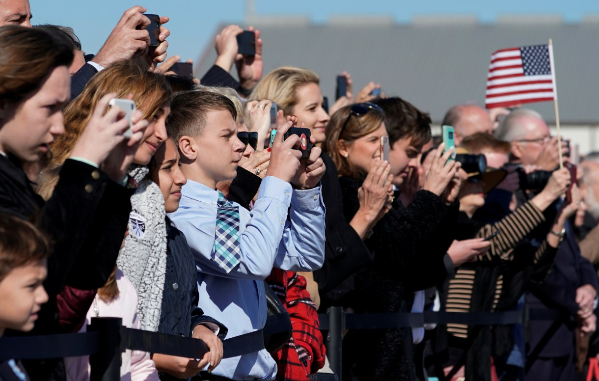 People watch the departure ceremony for the late former U.S. President George H.W. Bush at Ellington Field in Houston, Texas, U.S., December 3, 2018. (David J. Phillip/Pool via REUTERS)