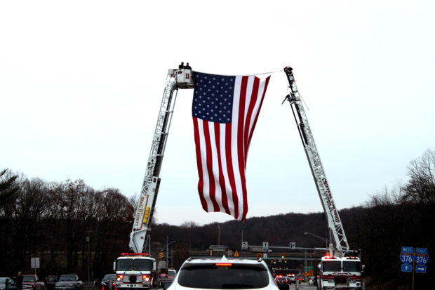 Ladder trucks from volunteer fire departments hoist a giant American flag above the honor escort for the family of Staff Sgt. Dylan Elchin as it merges on to Interstate 376 in Chippewa, Pennsylvania on Dec. 6, 2018. (Will Racke/TheDCNF)