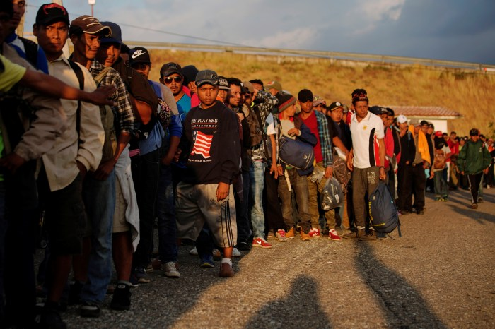Migrants wait in line to get transportation during their journey towards the United States, in Ingenio Santo Domingo