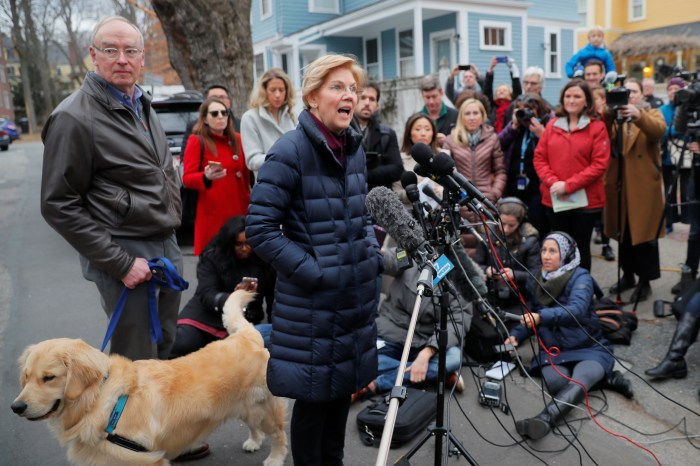 U.S. Senator Warren is joined by her husband Bruce and dog Bailey as she speaks to reporters in Cambridge