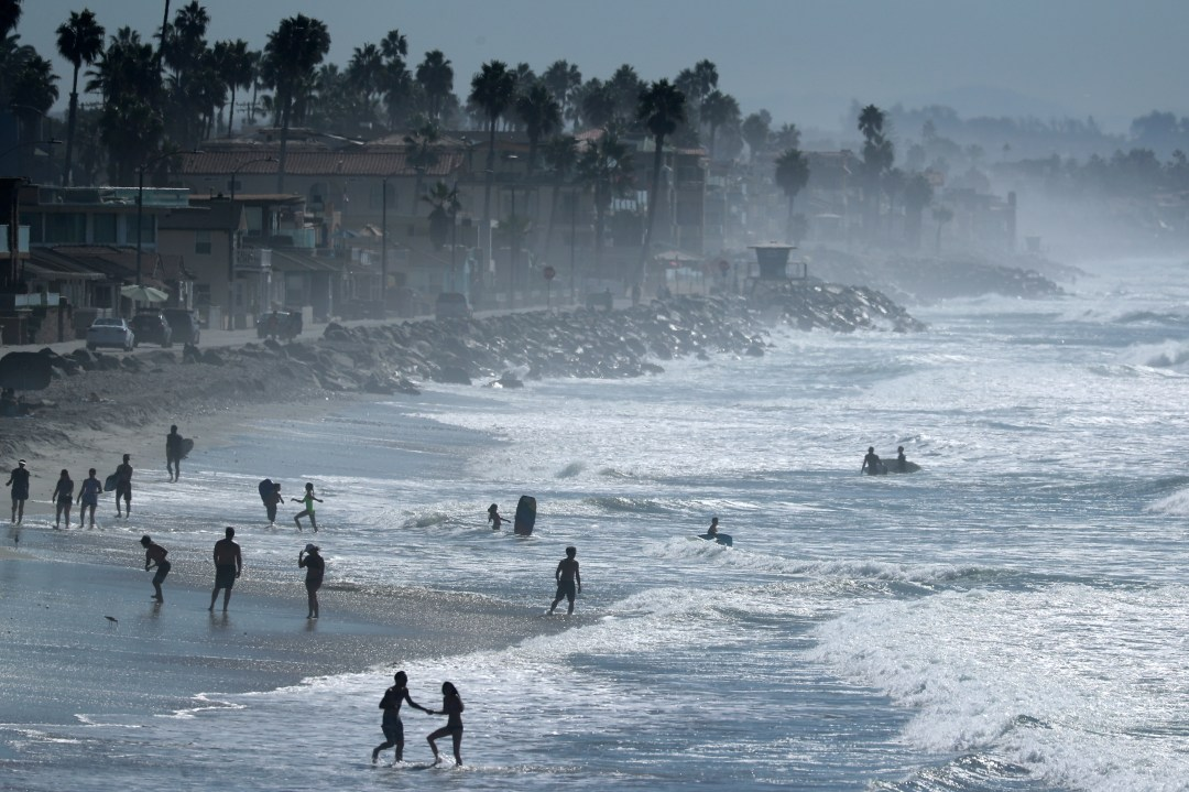 People cool off at the beach during a Southern California heat wave in Oceanside, California