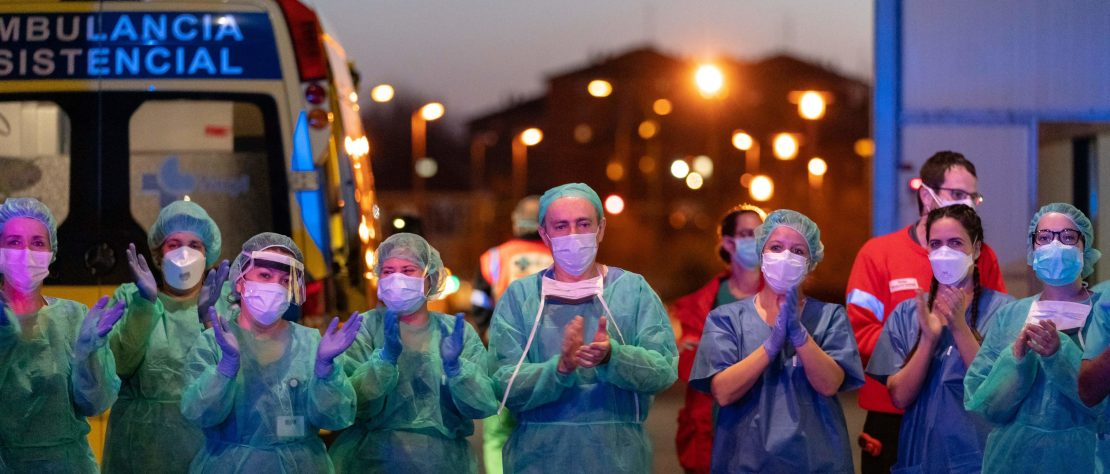 Healthcare workers dealing with the new coronavirus crisis applaud in return as they are cheered on by people outside the Burgos general hospital in Burgos on March 25, 2020. - (Photo by CESAR MANSO/AFP via Getty Images)