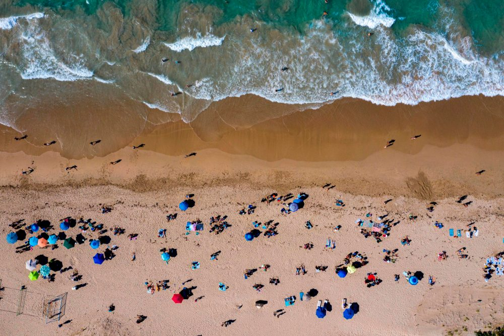 People are seen on the beach in San Juan Puerto Rico on March 15, 2020. (Ricardo Arduengo/AFP via Getty Images)