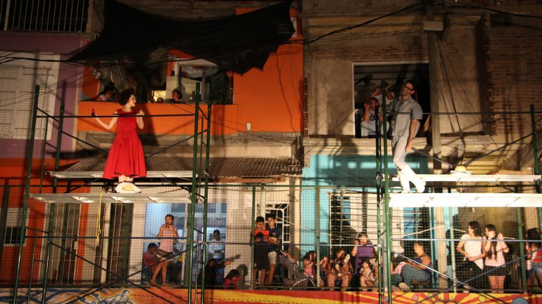 En plena acción, dos protagonistas de la ópera, con los vecinas disfrutando en la vereda y en las ventanas