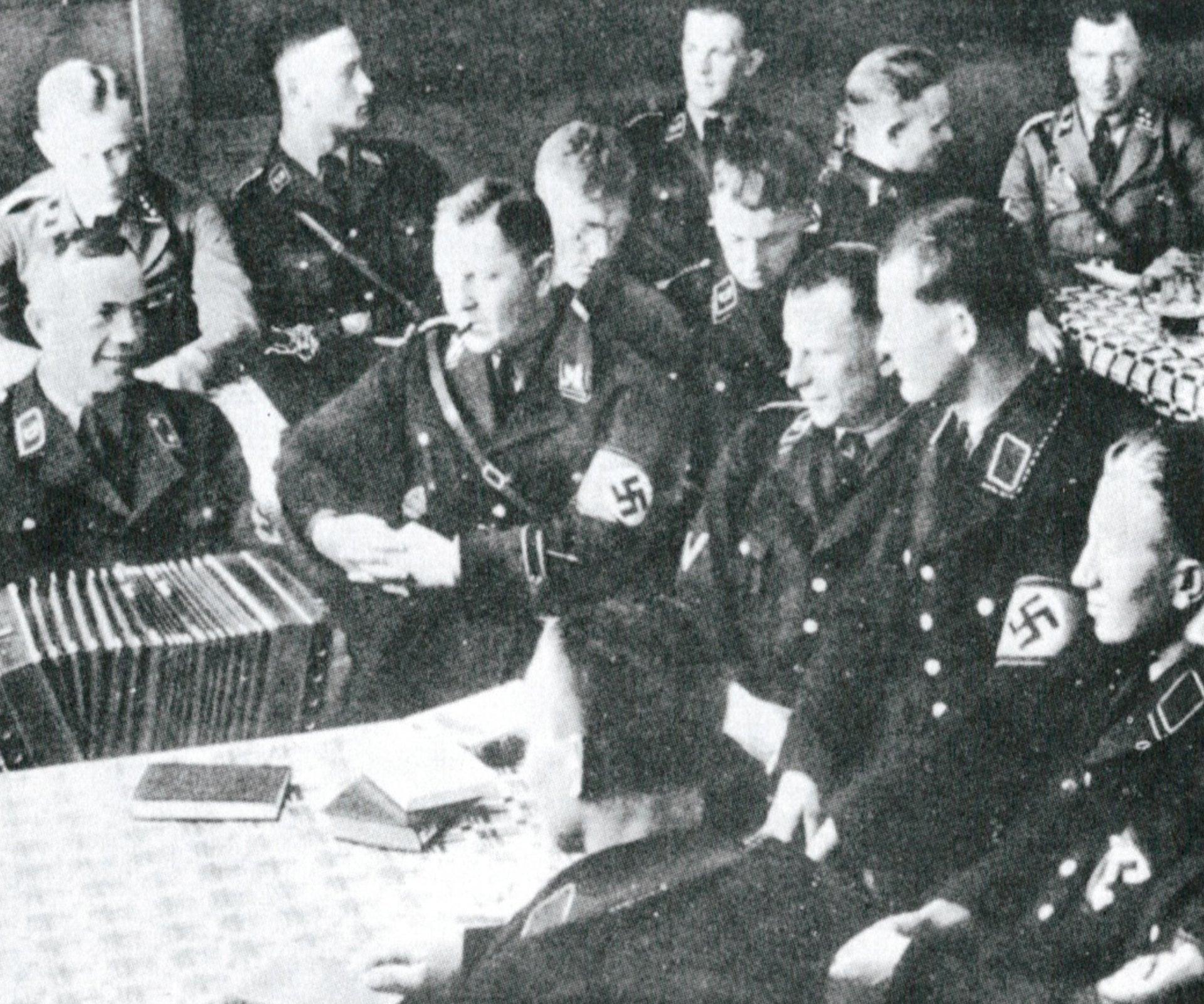 Theodor Eicke (en el centro, con un cigarrillo) preside una velada de camaradas celebrada en Dachau en 1934.