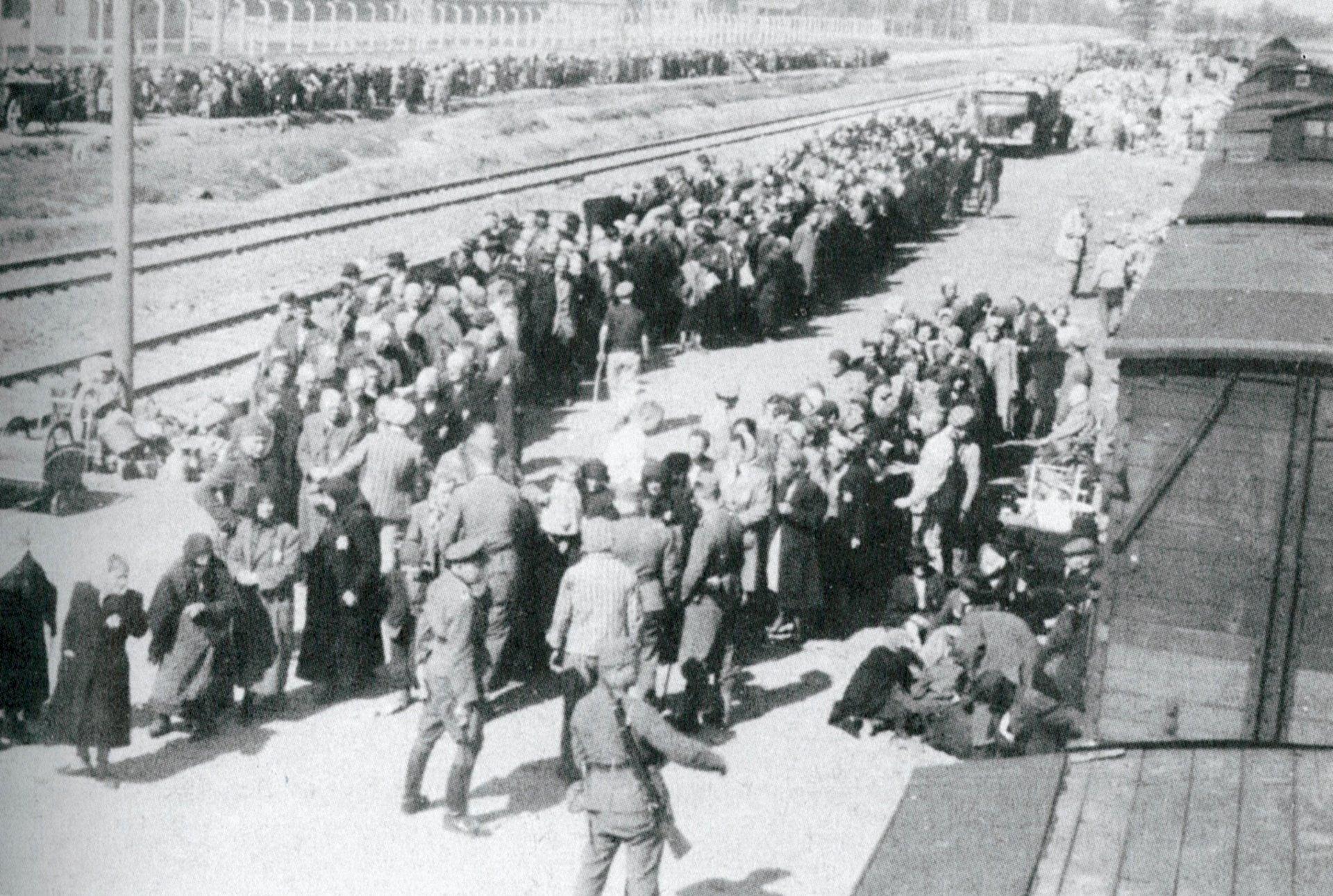 un médico de la SS (de uniforme en el centro) supervisa la selección de 3.500 judíos deportados de la Rutenia subcarpática a Auschwitz - Birkenau en mayo de 1944. A los que han sido elegidos para el exterminio inmediato (al fondo) los conducen a las instalaciones crematorias.