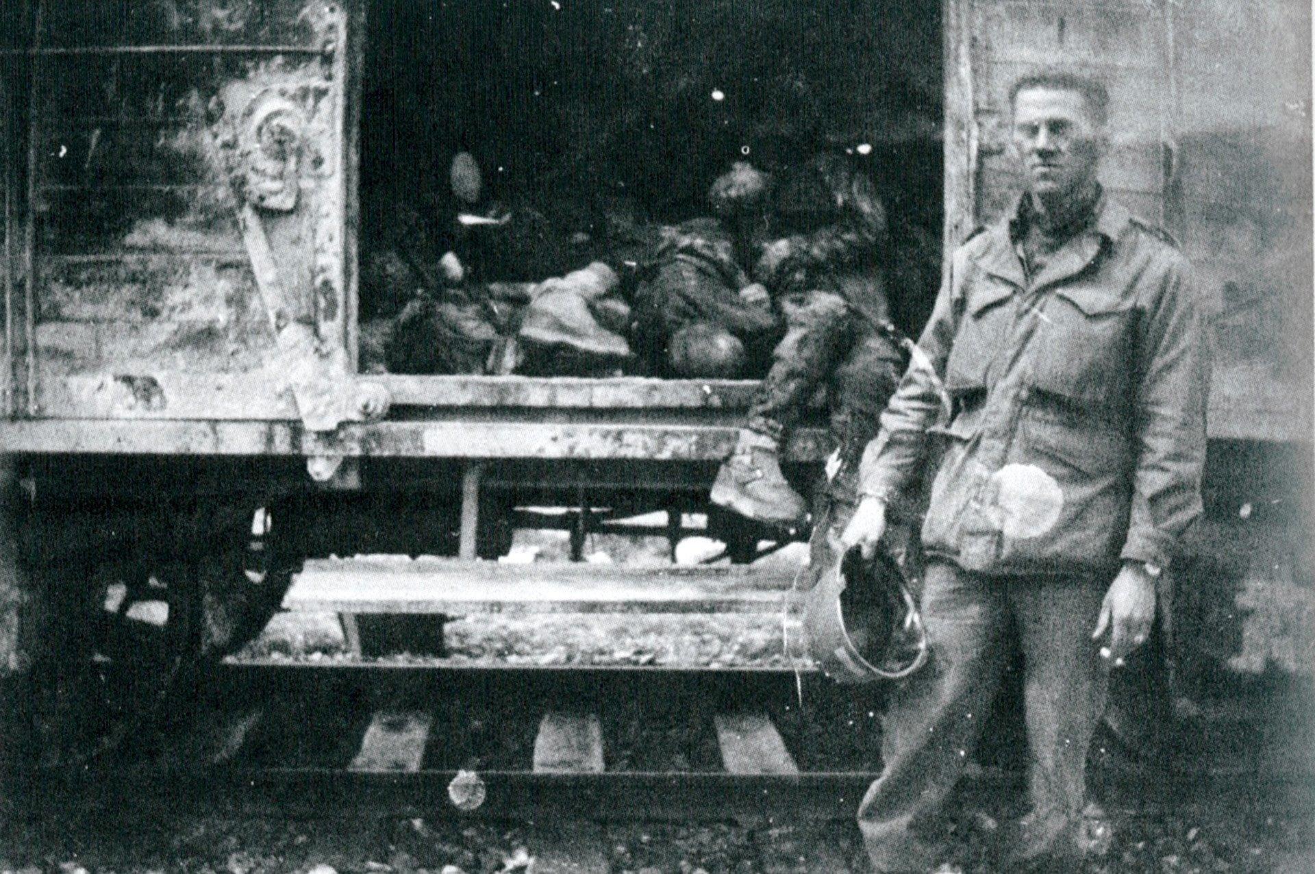 Soldado estadounidense ante un tren cargado de reclusos muertos , poco después de la liberación de Dachau. Habían salido de Buchenwald unas tres semanas antes.