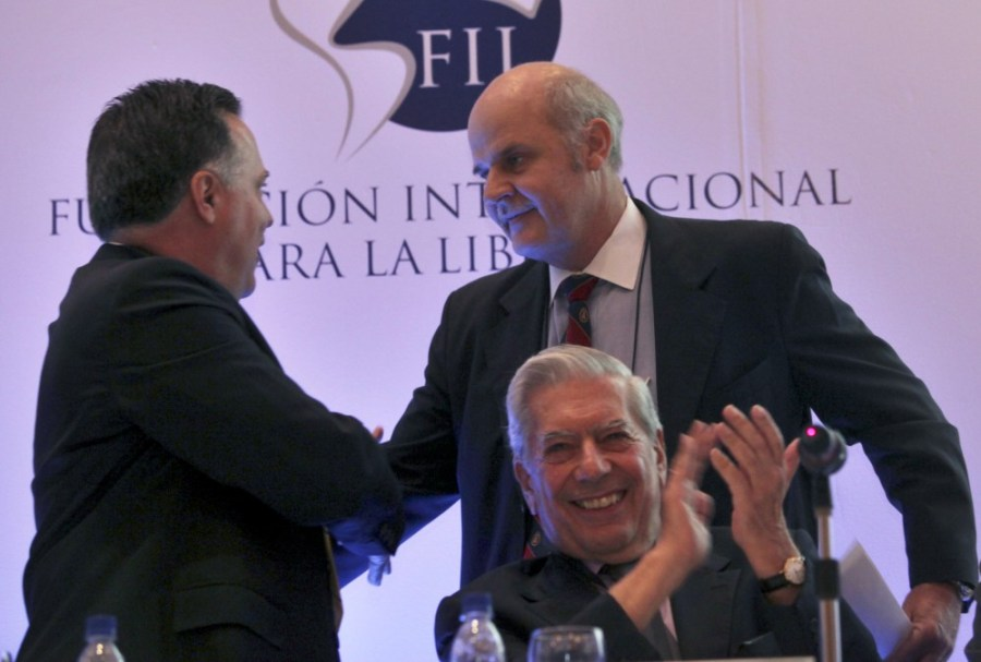 """Alejandro Chafuen, of the Atlas Economic Research Foundation, back right, shakes hands with Rafael Alonzo, of Venezuela's Freedom Center for Economic Studies, CEDICE, left, as Peruvian writer Mario Vargas Llosa applauds during the opening of the """"Freedom and Democracy"""" international forum in Caracas, Thursday, May 28, 2009.(AP Photo/Ariana Cubillos)"""