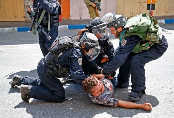 Israeli forces arrest a Palestinian youth during clashes between demonstrators and security forces in the city of Hebron in the Israeli-occupied West Bank, on July 28, 2017, as protests erupt in support of the Al-Aqsa mosque compound after Israeli police barred men under 50 from Friday prayers in the Old City of Jerusalem. Palestinians held mass prayers outside of a sensitive Jerusalem holy site after Israeli police barred men under 50 from entering following two weeks of tensions and deadly unrest. Despite fears of violent clashes around the Haram al-Sharif compound, known to Jews as the Temple Mount, the area was largely calm following Friday's midday prayers. / AFP PHOTO / HAZEM BADER (Photo credit should read HAZEM BADER/AFP/Getty Images)