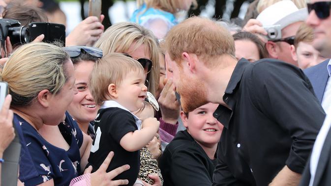 Pangeran Harry menyapa anak kecil saat berjalan di Taman Pemerintah Rotorua, Selandia Baru, Rabu (31/10). Pangeran Harry dan Meghan Markle sedang dalam tur tiga minggu di Australia, Selandia Baru, Tonga, dan Fiji. (Michael Bradley/Pool/AFP)