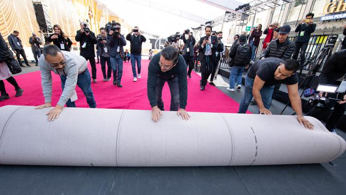 Kesibukan pekerja memasang karpet merah ajang bergengsi Academy Awards ke-92 atau Oscar 2020 di Hollywood & Highland, Hollywood, California, pada Rabu (5/1/2020). Academy Awards ke-92 akan berlangsung pada 9 Februari 2020 waktu setempat atau 10 Februari waktu Indonesia. (VALERIE MACON / AFP)