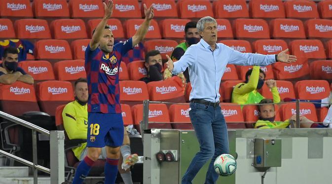 Pelatih Barcelona, Quique Setien, memberikan arahan kepada pemainnya saat menghadapi Atletico Madrid pada laga lanjutan La Liga pekan ke-33 di Camp Nou, Rabu (1/7/2020) dini hari WIB. Barcelona bermain imbang 2-2 atas Atletico Madrid. (AFP/Lluis Gene)