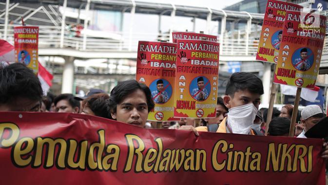 Massa yang tergabung dalam aliansi mahasiswa dan pemuda relawan cinta NKRI menggelar aksi unjuk rasa di depan Gedung Bawaslu, Jakarta, Jumat (17/5). Dalam aksinya mereka menolak Gerakan People Power karena syarat dengan kepentingan politik inkonstitusional. (Liputan6.com/Faizal Fanani)