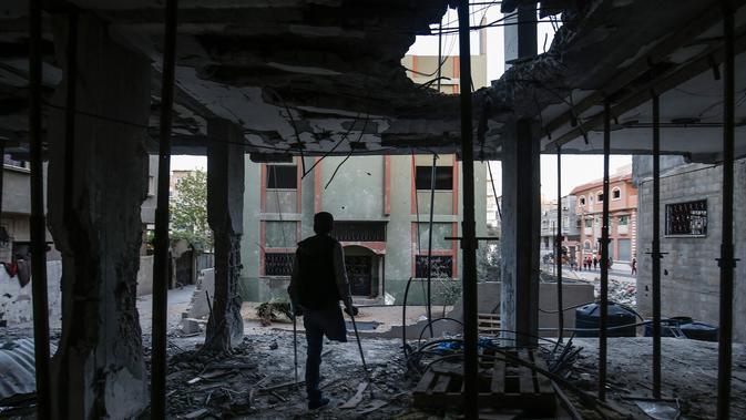 Seorang warga Palestina yang diamputasi berdiri di antara puing-puing sambil menunggu buka puasa di sebuah pusat komunitas yang hancur selama eskalasi dua hari, di Rafah, Jalur Gaza selatan (8/5/2019). (AFP Photo/Said Khatib)