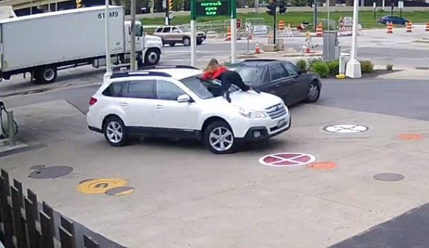 Woman jumps on moving car