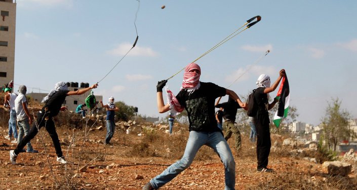 Palestinians throw stones during clashes with Israeli soldiers on the 13th anniversary of the second Palestinian Intifada.